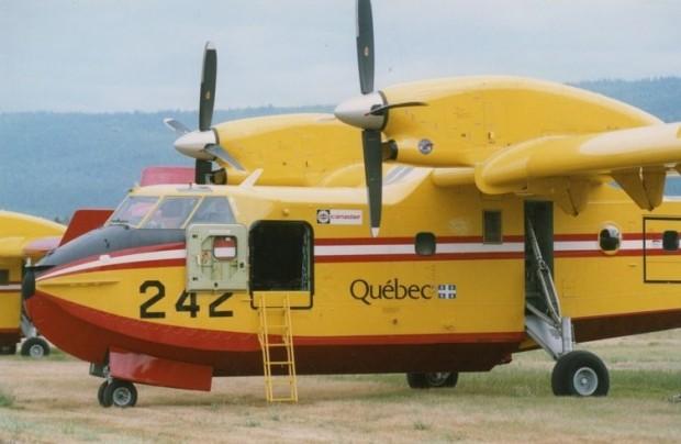 Avion jaune avec rayures rouges et blanches, doubles propulseurs, numéro 242 et Québec inscrits sur le fuselage.