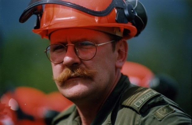 Homme moustachu avec lunettes, en uniforme vert coiffé d'un casque de sécurité, regarde la caméra en clignant des yeux.
