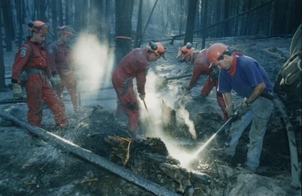 Deux pompiers en combinaison rouge creusant le sol brûlé. Un homme portant un t-shirt violet asperge le sol. Deux hommes observent. Tous portent des casques de sécurité.