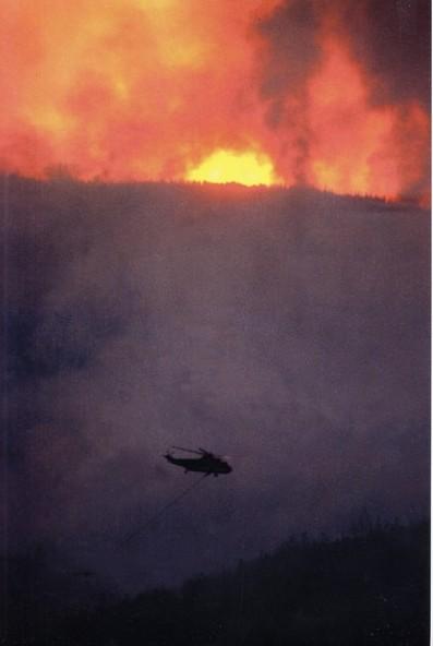 Un hélicoptère transportant un seau d'eau s'approche du feu.
