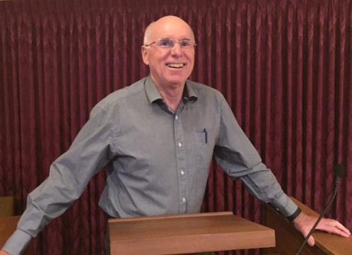 Homme vêtu d'une chemise grise debout derrière un lutrin.