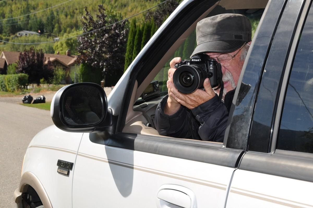 Un photographe prenant une photo assis dans son véhicule.