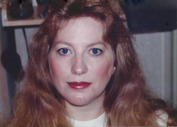 Portrait d'une femme à l'air sérieux aux cheveux roux et aux yeux bleus.