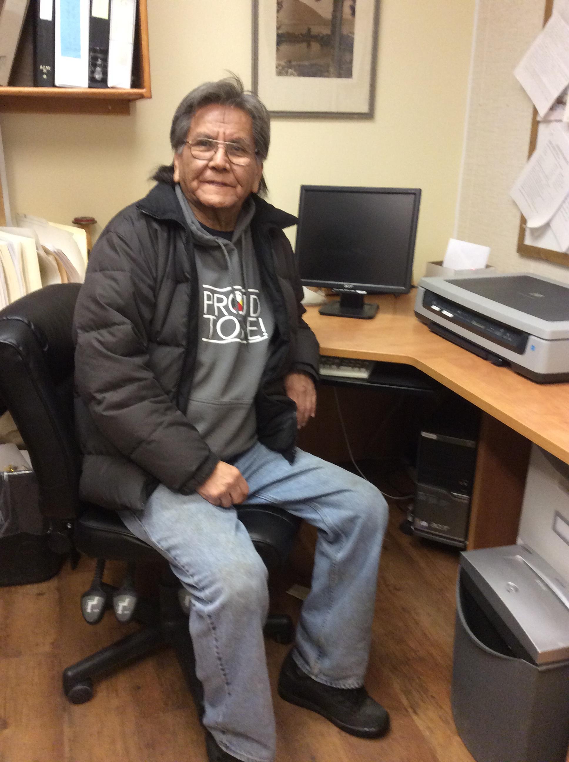Homme souriant, vêtu d'un manteau d'hiver, assis à un bureau d'ordinateur.