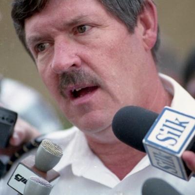 Homme moustachu, vêtu d'une chemise blanche, parle dans des microphones.