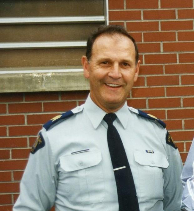 Appuyé sur un mur, un policier sourit vers la caméra.