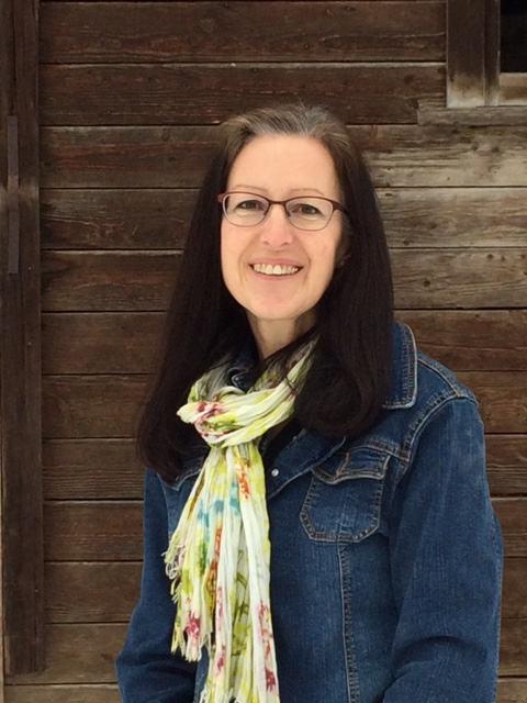 Femme avec lunettes, souriante vêtue d'un veston jean.