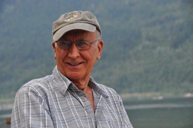 Homme souriant coiffé d'une casquette, lac et collines en arrière-plan.