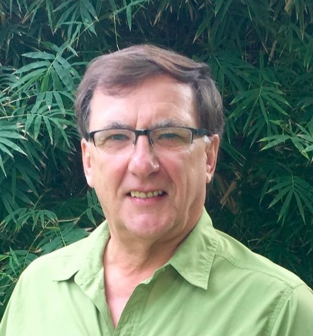 Photo d'un homme aux cheveux foncés avec lunettes, souriant.