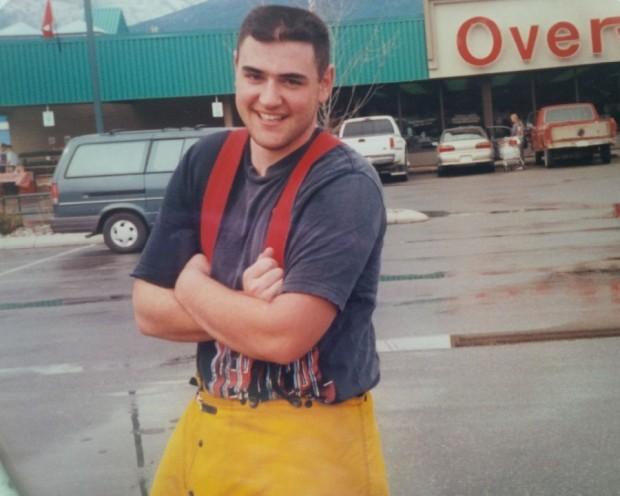 Debout dans un stationnement mouillé, jeune homme souriant portant des pantalons imperméables jaunes et des bretelles.