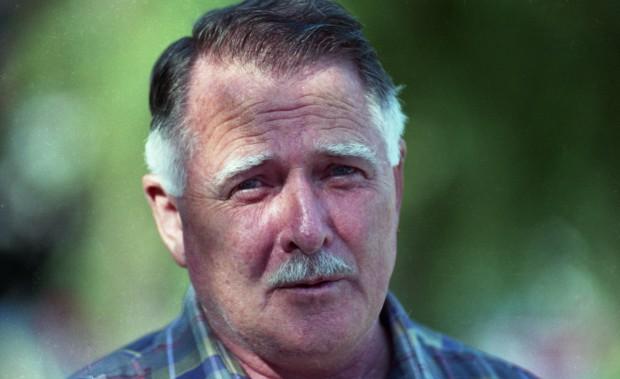 Homme moustachu à cheveux grisonnants, ayant l'air inquiet, vêtu d'une chemise à carreaux.