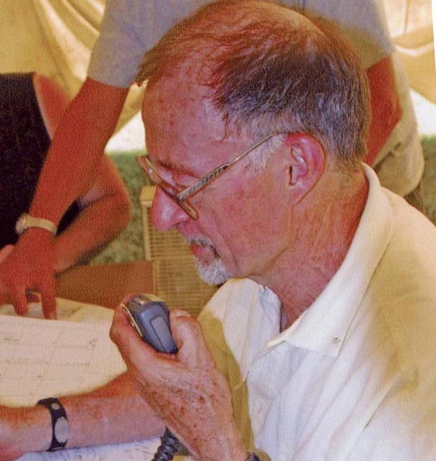 Homme avec barbichette et lunettes  parle dans un radiotéléphone.