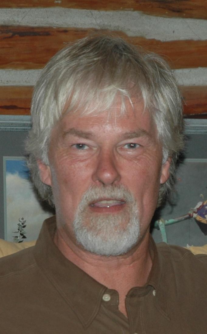 Homme aux cheveux gris avec barbiche regardant vers la caméra.