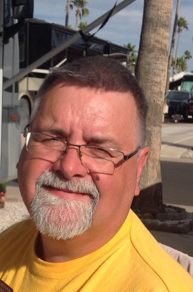 Homme avec une barbiche et lunettes sourit.