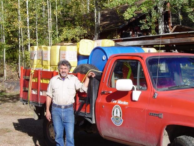 Homme à côté d'un camion rouge rempli de matériel.