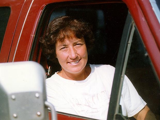 Femme assise dans un camion rouge, côté passagers.