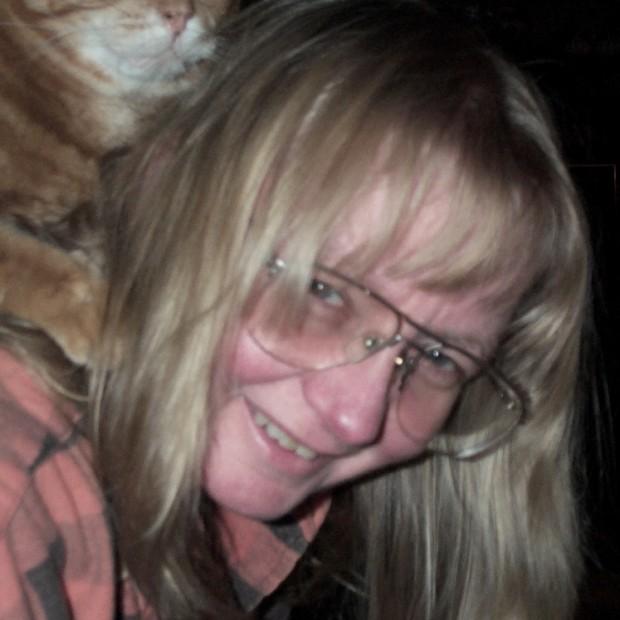 Une femme blonde portant lunettes avec un chat sur ses épaules.