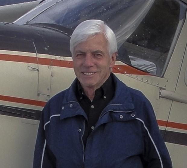 Photo d'un homme aux cheveux gris près  d'un avion.
