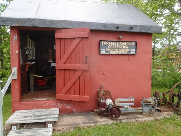 Un petit bâtiment rouge en métal et la porte y donnant accès. Une pompe de Hawboldt se trouve devant avec une pancarte qui indique : « Forman Hawboldt Collection ».