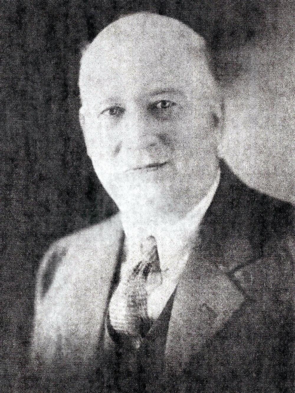 Une photo noir et blanc de Forman Hawboldt montrant un homme dégarni aux yeux espacés, à l'air sympathique en costume cravate.