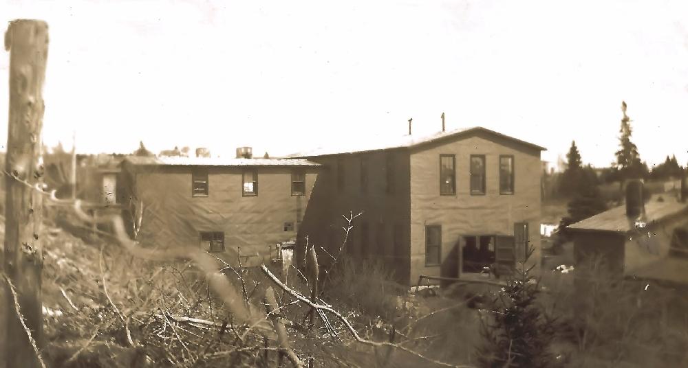 Une photo couleur sépia the Hawboldt Gas Engines montrant à gauche le bâtiment principal de deux étages sur la rue North ainsi que l'atelier de fabrication qui lui est adossé et qui descend abruptement sur la berge du ruisseau. Un autre bâtiment à droite et au premier plan est la fonderie avant qu'il ne soit remplacé par un bâtiment au toit arrondi.