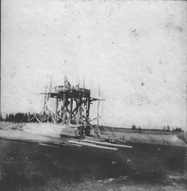 Une photo noir et blanc montrant la charpente du château d'eau en construction. On peut voir des piles de bois au premier plan et le talus de la voie ferrée de la Halifax and Southwestern Railway à l'arrière-plan. Le château d'eau devait fournir l'eau pour le système de canalisations d'eau du village et pour les trains.