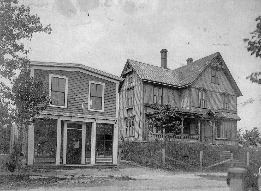 Une photo en noir et blanc de la bijouterie à deux étages proche de la route avec deux devantures et une porte au centre. L'étage supérieur a deux petites fenêtres. A droite, sur un talus, en retrait par rapport à la route, avec une clôture grillagée, près de la rue, une maison à bardeaux de trois étages. Des marches mènent à la porte d'entrée, des fenêtres mansardées à droite des marches de la façade et une véranda devant la façade gauche de la maison. La maison est ornée de dentelle de bois, de nombreuses fenêtres et d'un toit très pentu.