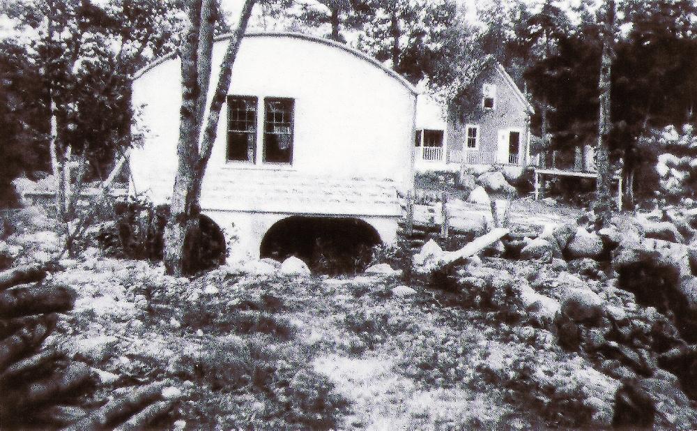 Une photo en noir et blanc montrant le toit arrondi de la centrale électrique sur la East River et la rivière s'écoulant sous la centrale. A droite de la centrale, on peut voir une petite maison où habitait avec sa famille l'opérateur de la centrale.