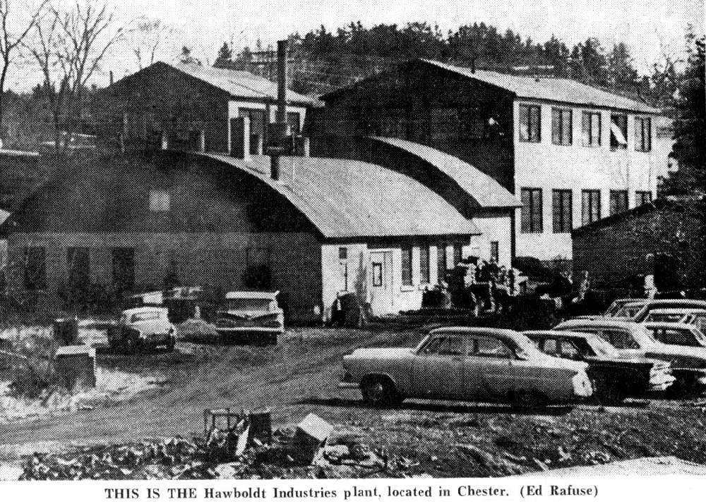 Une photo en noir et blanc de l'entreprise montrant le bureau sur la rue North. A l'arrière-plan se trouvent l'atelier de fabrication de deux étages ainsi que, à gauche de l'atelier, les bâtiments pour la fonte et le soudage au toit arrondi. Le parking des employés est au premier plan à côté du ruisseau.
