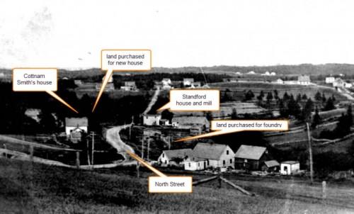 Une photo en noir et blanc montrant l'extrémité ouest de la rue North à Chester, le terrain de la fonderie et la résidence sont indiqués. La route   traverse la photo, la maison de Cottnam Smith est à gauche et la propriété de la maison de Hawboldt plus à l'est au-delà de son terrain. Sur le côté droit de la route en face de la maison de Smith et à l'est de la maison de Stanford se trouvent le terrain de la fonderie et le ruisseau venant du lac Stanford.