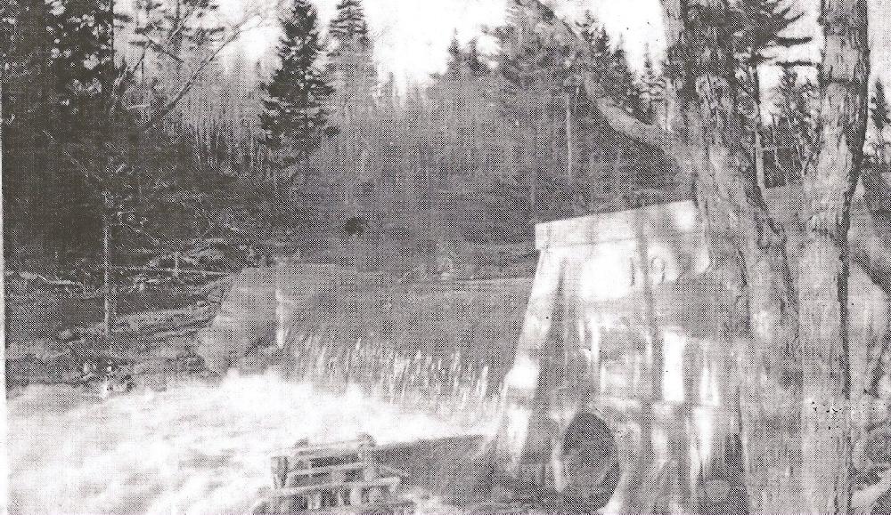 Une photo en noir et blanc qui montrant l'eau passant au-dessus du barrage de Chester Electric sur la East River. La date de 1919 est inscrite sur ce barrage en béton.