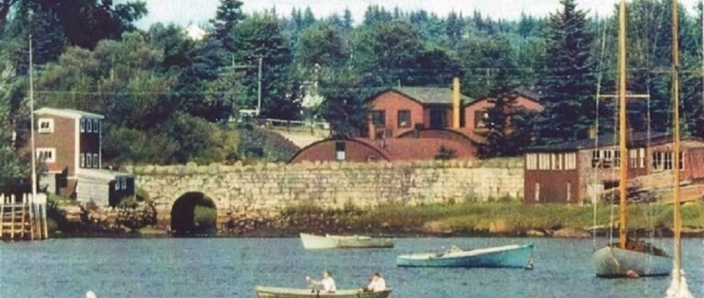Une photo couleur avec des bateaux au premier plan   prise   de Mill Cove en direction de Hawboldt Gas Engines. On peut voir le vieux pont de pierre, le bâtiment rond et rouge de la fonderie, l'atelier et le bureau principal. Un bâtiment à gauche du pont servait d'entrepôt. Les bâtiments rouges de l'autre côté du pont étaient une menuiserie. Le ruisseau prenait sa source dans le lac Stanford. Il permettait d'alimenter en électricité la fonderie et fournissait de l'eau au système de canalisations d'eau du village. Il se jetait dans Mill Cove sous le vieux pont de pierre.