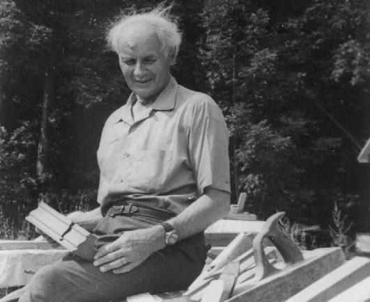 Photographie noir et blanc de François-Xavier Lachance, âgé, assis à l'extérieur sur une pile de matériaux, tenant une moulure en bois.