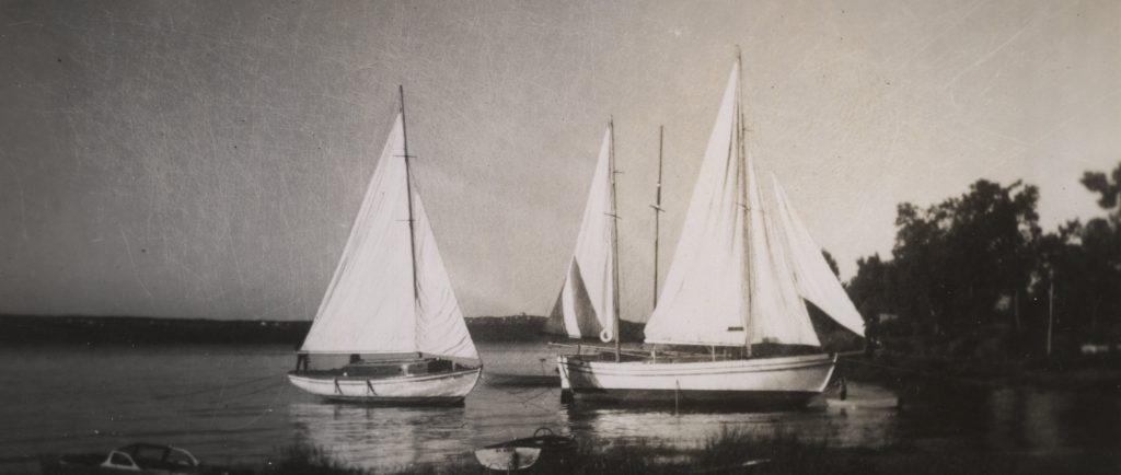 Photographie noir et blanc de trois yachts blancs, aux voiles hissées, ancrés près de la rive.