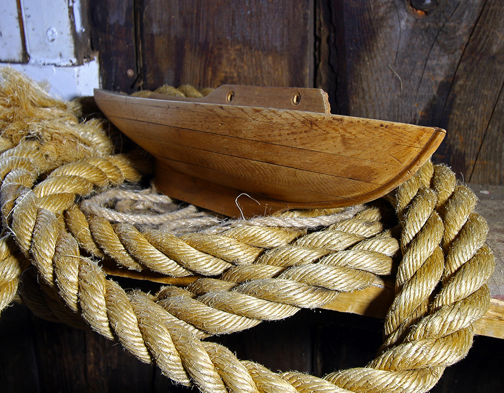Photographie couleur d'une demi-coque en bois, vue de profil. L'objet est posé sur des cordages de bateaux.