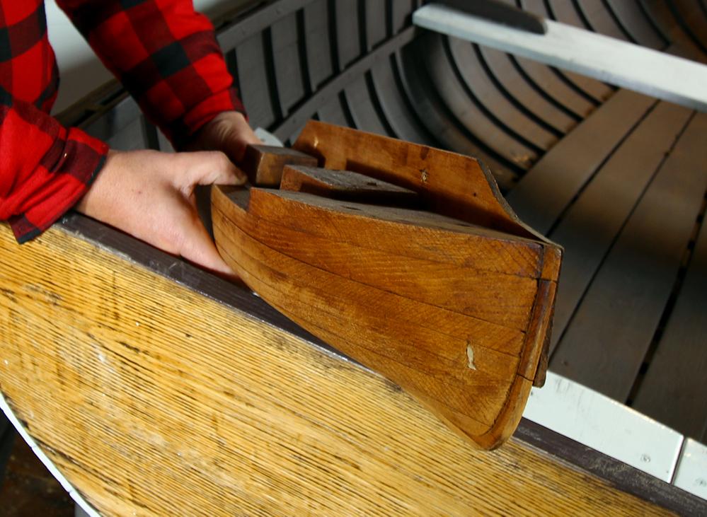 Photographie couleur d'une demi-coque en bois, vue de face.