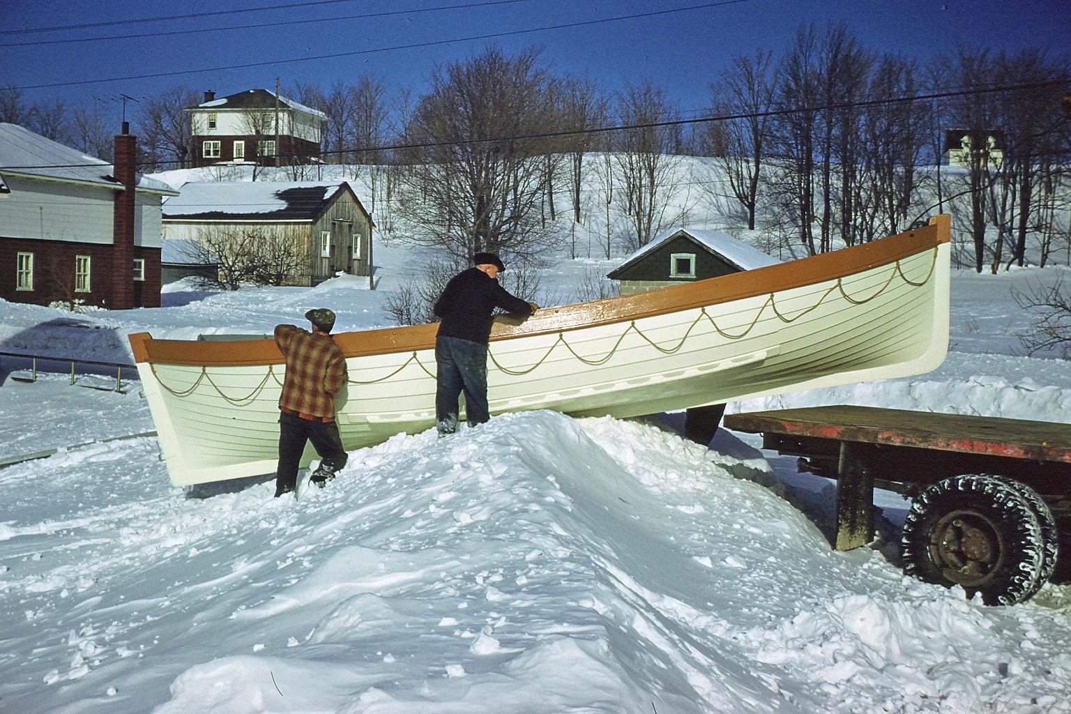 Photographie couleur où deux hommes, un jeune et un âgé, glissent une chaloupe blanche sur un amas de neige afin de l'installer sur la plate-forme arrière d'un camion.