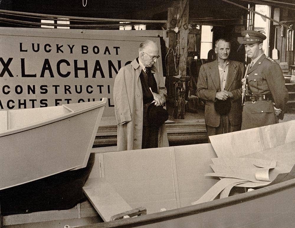 Photographie noir et blanc où trois hommes se tiennent dans une chalouperie. Une enseigne portant l'inscription « Lucky boat. FX. Lachance. Construction de yachts et chaloupes » est partiellement visible derrière eux. Les hommes de gauche (le Gouverneur général) et de droite (un militaire) regardent les embarcations. F-X Lachance est au centre, tenant un chapeau.