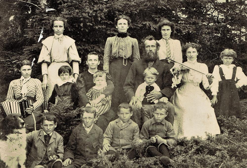 Photographie noir et blanc montrant les parents de François-Xavier Lachance, leurs 13 enfants et leur chien. Tous regardent la caméra, assis ou debout devant un boisé.
