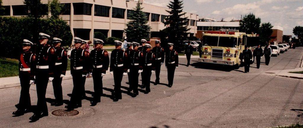 De nombreux membres de la garde d'honneur marchent en uniforme de grande tenue, devant un camion d'incendie jaune, en tête du cortège funèbre de Morley James.