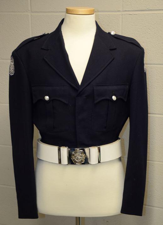 Uniforme original de grande tenue numéro un de la garde d'honneur  Veste noire de style combat munie de l'insigne du service d'incendie de Calgary sur chacune des épaules, de deux pochettes à la hauteur de la poitrine, de plis creux, de rabats festonnés et de deux épaulettes fixées à l'aide de boutons argentés Ceinture en cuir blanche et boucle plaquée argent sur la veste portée par un mannequin blanc sans tête