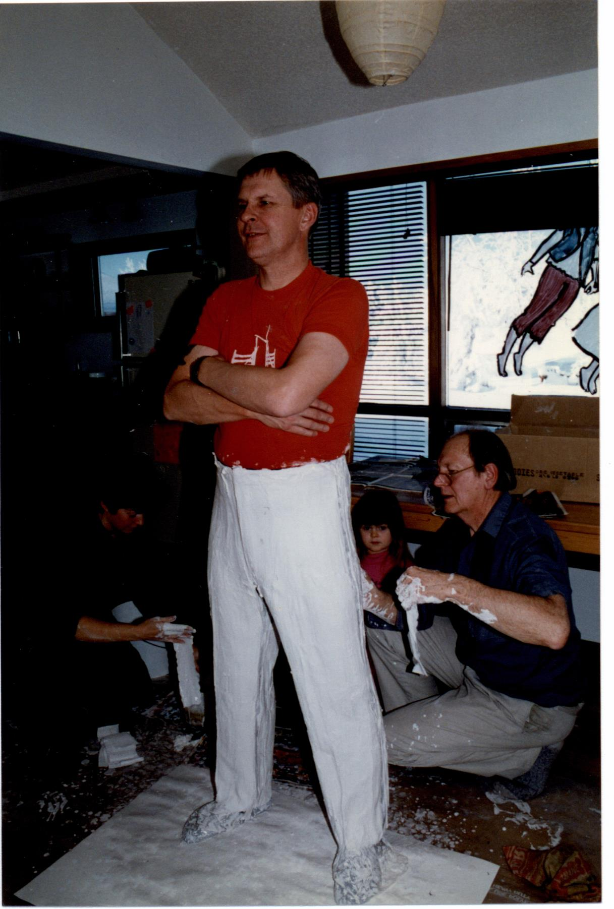 Rick Choppe se tient les bras croisés pendant que l'artiste, accroupi, met du plâtre sur ses jambes.