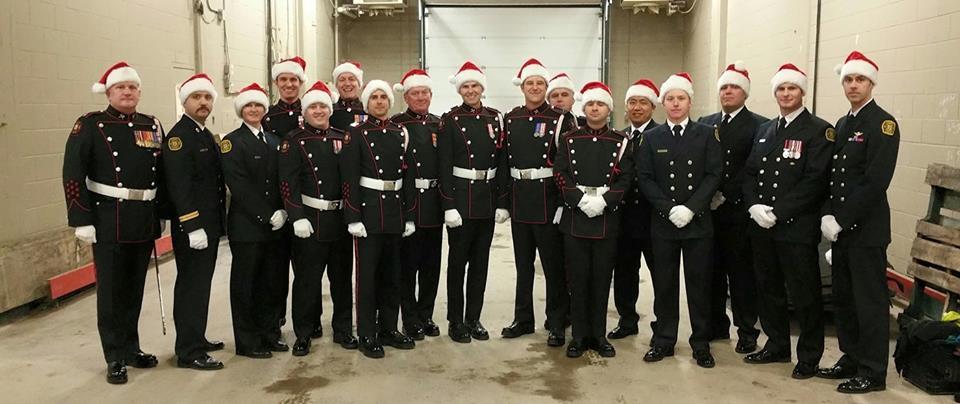 Dix-sept pompiers en uniforme de grande tenue, souriant dans les coulisses, avec chapeau rouge de père Noël