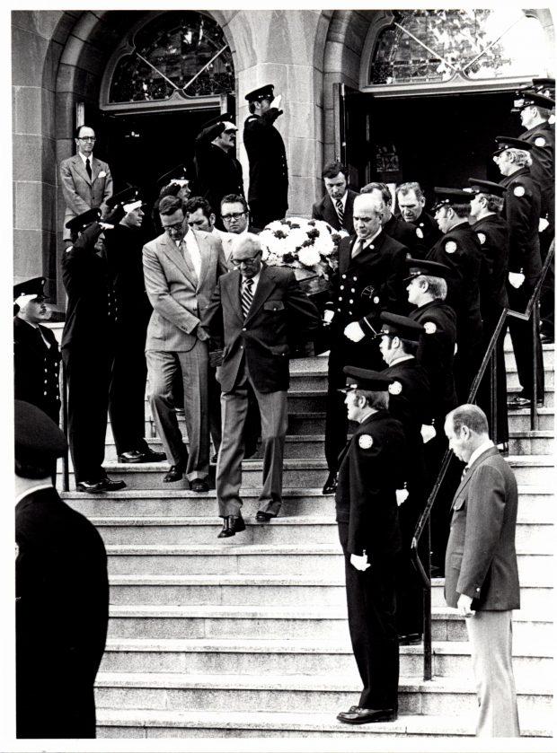 Les porteurs sortent de l'église avec le cercueil de David Allan. Des pompiers en uniforme se tiennent au garde-à-vous