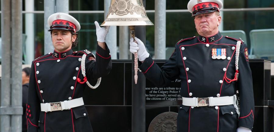 Deux membres de la garde d'honneur en uniforme de grande tenue avec gants blancs s'occupent de faire sonner et de tenir la grosse cloche suspendue à la place de l'hommage (Tribute Plaza), hôtel de ville.