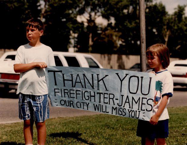 Deux enfants tiennent une bannière sur le trajet du cortège funèbre. « Merci, pompier James. Vous allez manquer à notre ville. »