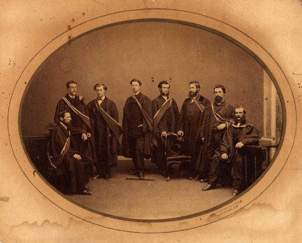 Photo de 8 étudiants en médecine de l'université Queen, 1865 portant leurs robes académiques