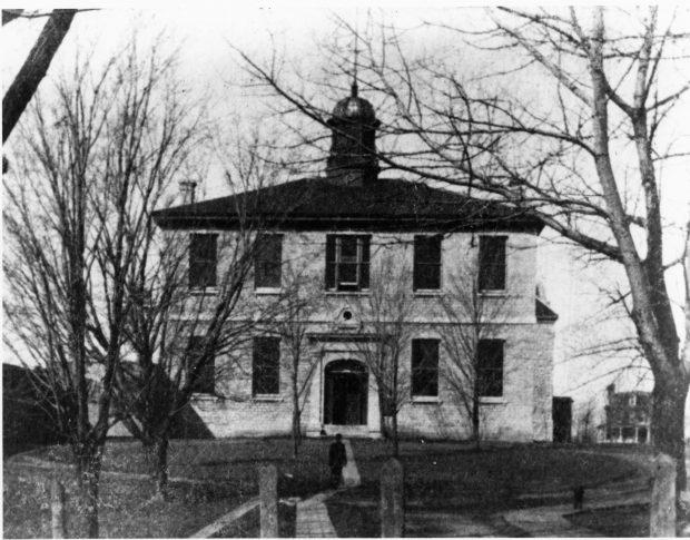 Photo de l'édifice médical de Queen vers 1880 avec des arbres et un individu devant.