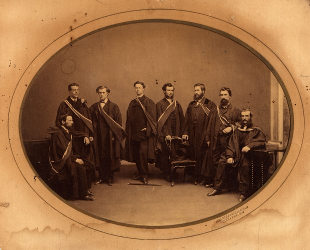 Photo de 8 étudiants en médecine de l'université Queen, 1865 portant leurs robes académiques