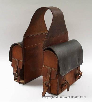 Sac de selle de médecin en cuir. Deux sacoches carrées sont reliées ensemble par une sangle de cuir se plaçant par dessus le cheval.